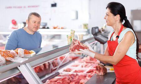 Photo pour Woman seller helping male customer choosing meat in butcher's shop - image libre de droit