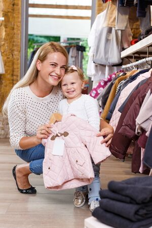 Photo pour Cheerful young woman and her little daughter shopping in kids clothing store - image libre de droit