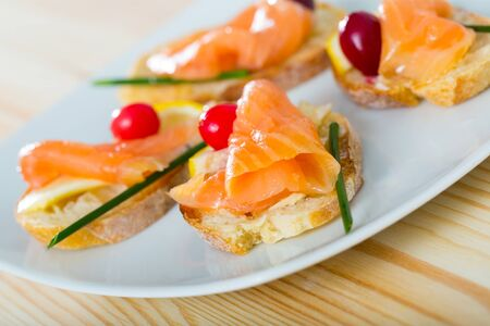 Photo pour Image of exquisitely served tasty bruschettes with salmon, butter and cranberries - image libre de droit