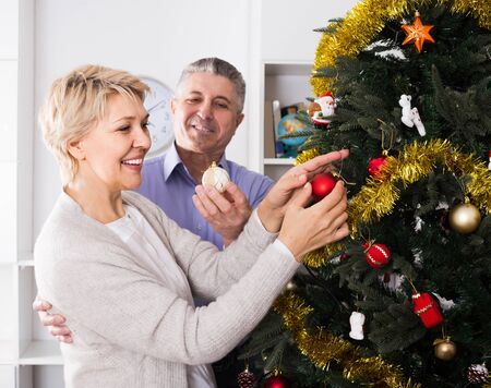 Mature happy european couple preparing to celebrate in his home Christmas and New Year