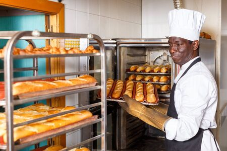 Photo pour Experienced baker working in small bakery, taking out bread from industrial oven and putting on rack - image libre de droit