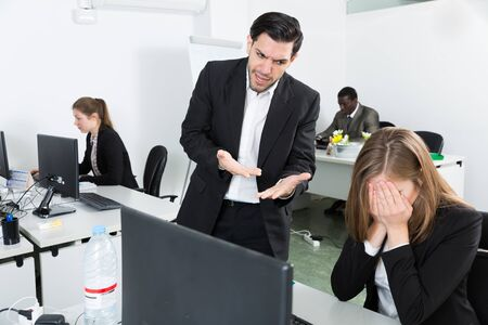 Photo for Angry male boss pointinting to misses in work to female  manager working at laptop - Royalty Free Image