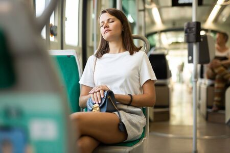 Photo pour Portrait of young woman going to work by bus or trolley at early morning sitting with closed eyes - image libre de droit