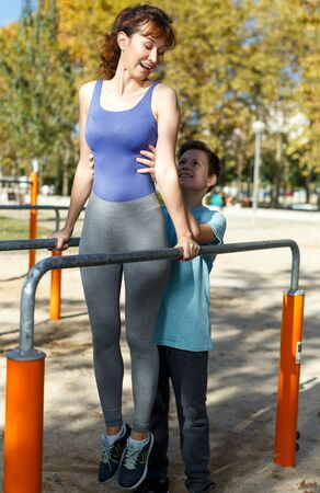 Foto de Smiling sportive woman and teenage boy exercising together on parallel bars on sports ground at sunny autumn day - Imagen libre de derechos