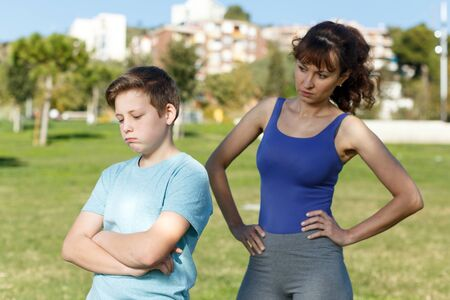 Photo pour Portrait of upset teen boy in sportswear scolded by mother at sports ground - image libre de droit