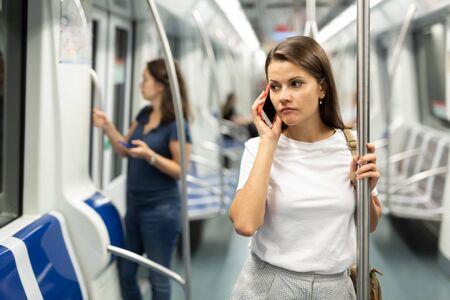 Photo pour Woman talking on a cell phone in a subway car - image libre de droit
