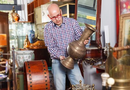 focused senoir man visiting shop of antique goods in search of interesting objects