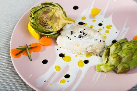 Foto de Deliciously fillet  of  fried horse-mackerel  with sauce and artichokes on plate - Imagen libre de derechos