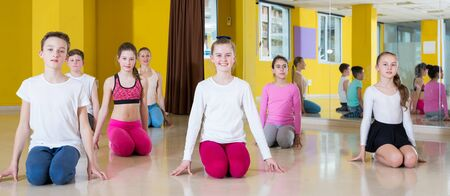 Teenage boys and girls practicing dance with female trainer in dance hall, sitting on floor