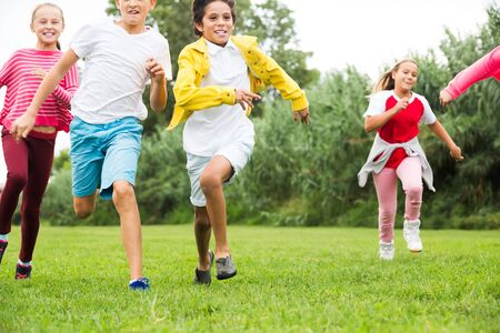 Photo pour Glad kids are jogging together in the park and having fun - image libre de droit