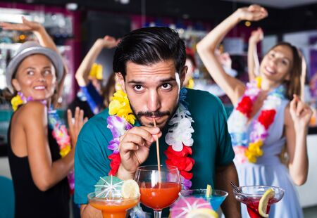Photo pour Adult man is drinking alcohol cocktail on the hawaiian party - image libre de droit