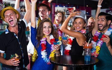 Photo pour Cheerful friends are dancing on the hawaiian party in bar - image libre de droit