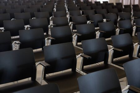 Empty conference hall with rows of black plastic chairs