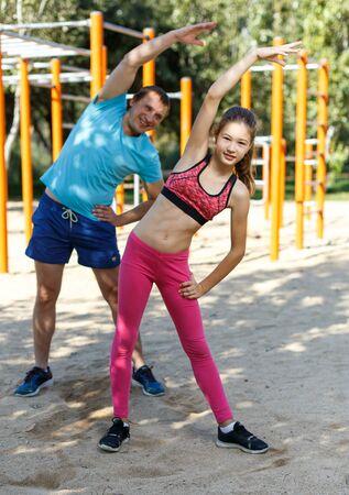 Foto de Smiling sporty tweenager girl doing exercises with her father in summer park - Imagen libre de derechos