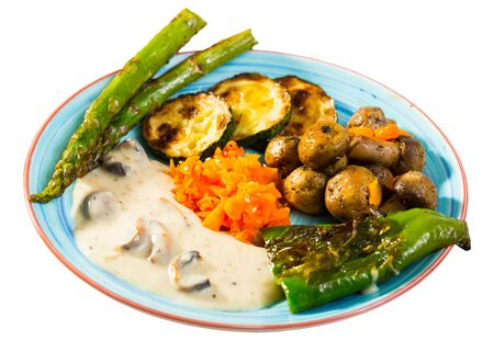 Photo pour Healthy meal - baked mushrooms, zucchini, asparagus, bell pepper, carrots with vegan sauce. Isolated over white background - image libre de droit