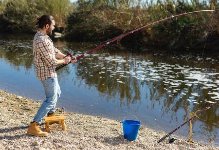 Photo pour Happy fisherman pulls fish out of the river - image libre de droit