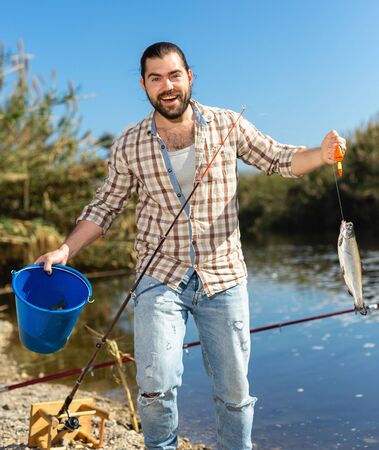 Photo pour Adult man standing near river and pulling fish expressing emotions of dedication - image libre de droit