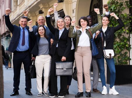 Portrait of multiracial group of enthusiastic business people emotionally gesturing and celebrating success, standing on city street