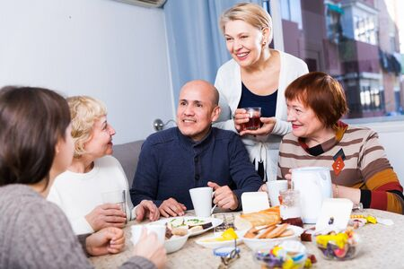 Photo pour Mature women and their friend are drinking tea and talking at home. - image libre de droit