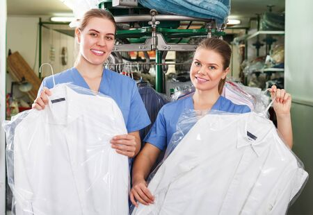 Photo pour Two confident smiling girls workers offering professional dry cleaning, showing clean clothing - image libre de droit