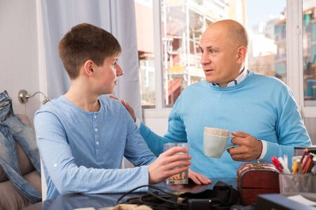 Photo for Happy father and teenage son enjoying conversation at home - Royalty Free Image
