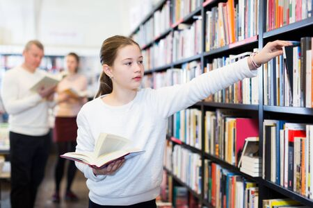 Photo for Smiling preteen child searching  of literature in bookstore on background of reading parents - Royalty Free Image