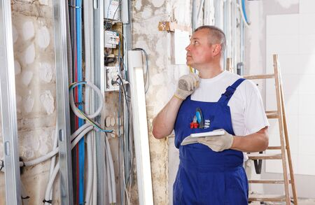 Photo pour Confident builder handyman examining room and planning construction works - image libre de droit