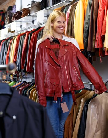 Photo for Portrait of smiling female customer with leather jackets in clothes store - Royalty Free Image
