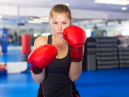 Photo pour Portrait of young woman boxer in red boxing gloves training in gym - image libre de droit