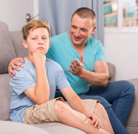 Photo for Adult man is asking forgiveness from his sad son after conflict at the home. - Royalty Free Image
