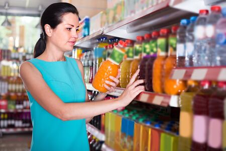 Photo pour Girl is holding bottle with juice in the shop. - image libre de droit