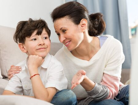 Photo pour Preteen boy upset about something and his mother gently soothing him at home. Concept of difficult age - image libre de droit