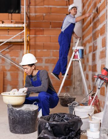 Photo pour Portrait of two professional builders in process of repair at private house - image libre de droit