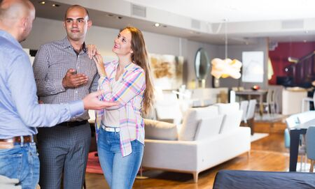 Photo pour Family couple choosing furniture for apartment in home furnishings store with help of salesman - image libre de droit