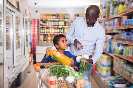 Photo pour Smiling African American man and son choosing products in food store during family shopping - image libre de droit