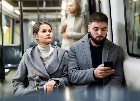 Photo pour Man and woman using phone inside tram - image libre de droit