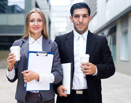 Photo for Businessman and his woman colleague in suit are standing with folder and coffee near the office. - Royalty Free Image
