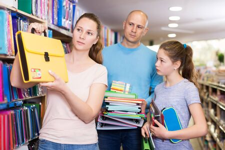 Photo pour Loving young  parents with daughter buying school supplies in stationery store - image libre de droit