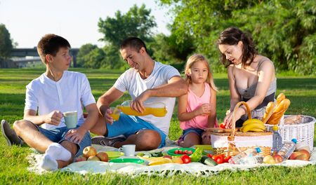 Photo pour Happy parents with two kids having picnic together on green meadow in park - image libre de droit