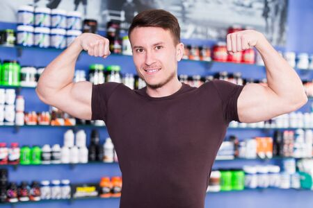 Photo for Cheerful athletic guy showing biceps in shop interior - Royalty Free Image