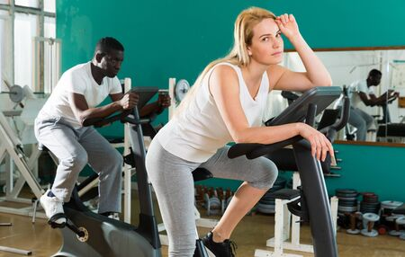 Photo for Portrait of tired young woman sitting on exercise bike at sport club - Royalty Free Image