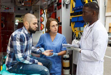 Photo pour Ambulance team providing medical care to patient on stretcher in ambulance car - image libre de droit