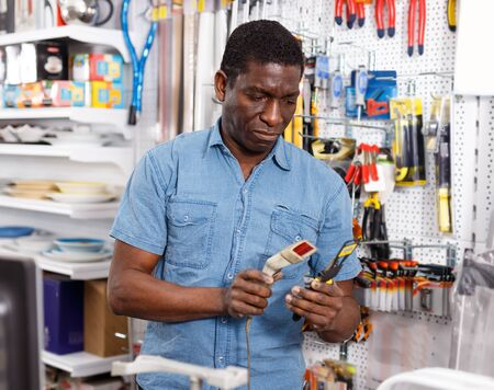 Photo pour Nice African American salesman working on computer behind counter in store of household goods - image libre de droit