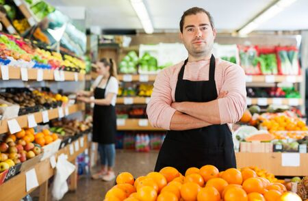 Photo pour Young man in apron selling fresh oranges and fruits on the supermarket - image libre de droit
