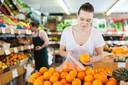 Foto für Young woman customer choosing fresh oranges  on the supermarket - Lizenzfreies Bild