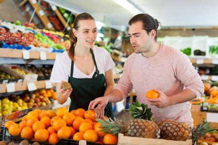 Photo pour Nice woman wearing apron selling fresh oranges to man customer in fruit store - image libre de droit
