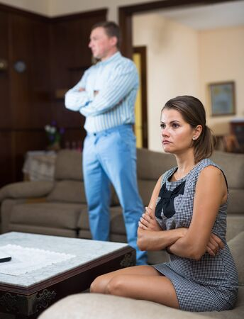 Photo pour Relationship difficulties. Upset young woman sitting on sofa at home on background with frustrated husband - image libre de droit