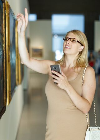 Photo pour Positive woman wearing glasses with smartphone standing in hall of picture gallery and pointing to invisible screen - image libre de droit