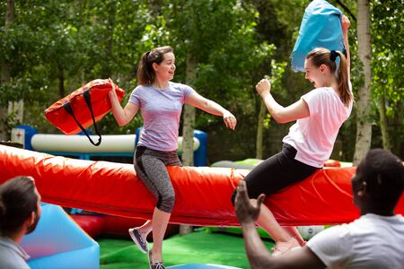 Photo pour Cheerful girlfriends fighting with inflatable pillows in an amusement park - image libre de droit