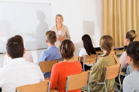 Foto de Mature female speaker giving presentation for students in lecture hall - Imagen libre de derechos